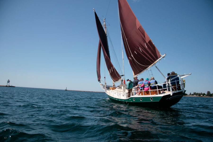 the schooner Hjordis sets sail towards blue skies on its way out of the Grand Marais harbor